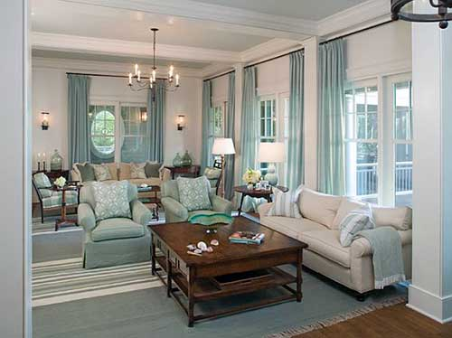 sala de estar com tapetes, cortinas e poltrona azul tiffany