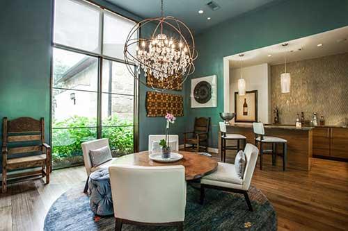 lustre moderno com iluminaçao parecida com velas em sala de parede verde