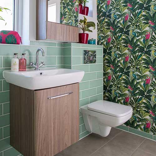 banheiro com parede em revestimento verde e parede em papel