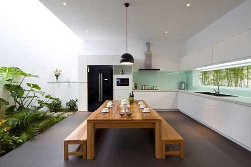 sala de jantar com mesa de madeira e jardim de inverno no canto