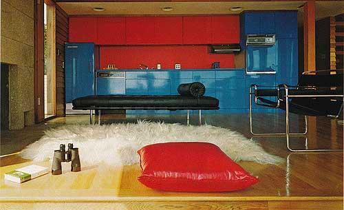 cozinha junto da sala de estar nas cores azul e vermelha