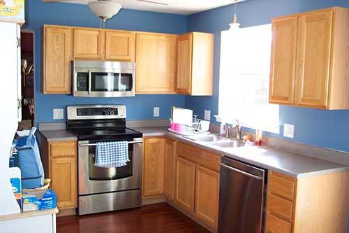 foto de cozinha com armarios de madeira e paredes azuis