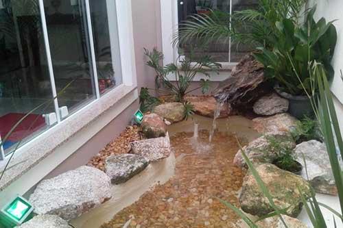 imagem jardim de inverno com fonte de agua visto da sala de jantar. imagem: atelier de paisagem