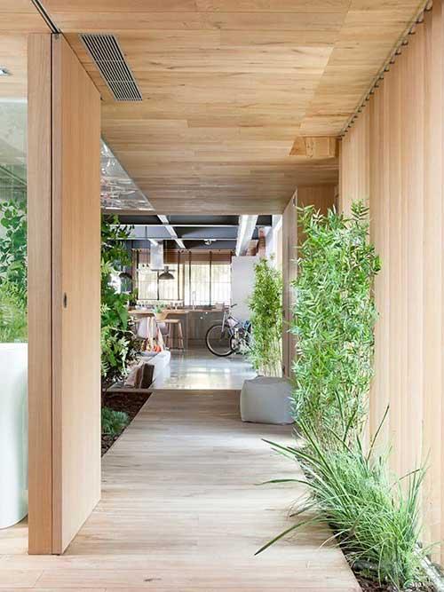 casa com decoracao em madeira e jardim de inverno no trajeto ate a sala de jantar