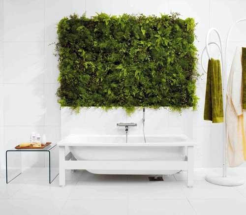 banheiro branco com parede verde feita pelo jardim vertical