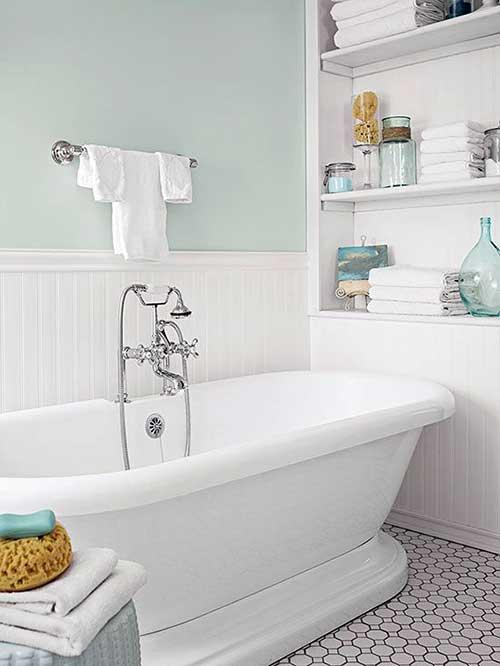 banheiro com parede verde clara e banheira branca