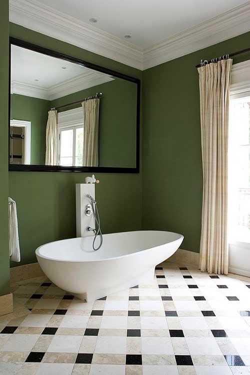 foto de banheira branca com parede do banheiro verde e piso geometrico