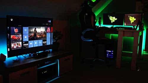 quarto gamer com luz apagada e leds coloridos