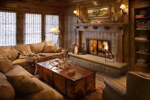 espaço decorado com cores marrom e material em madeira aliados a uma lareira rustica