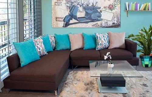 sala de estar com sofa marrom em l e almofadas azul turquesa