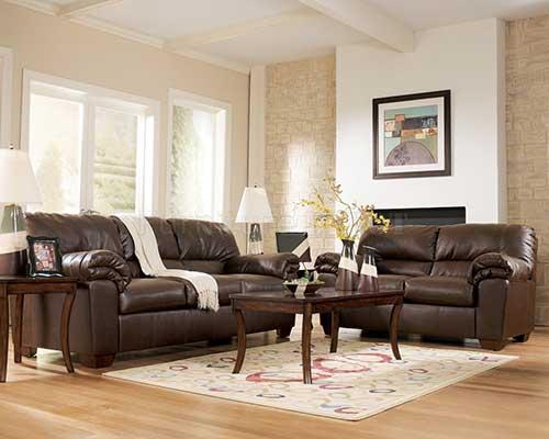 sala de estar com sofa marrom de couro e cores claras em volta