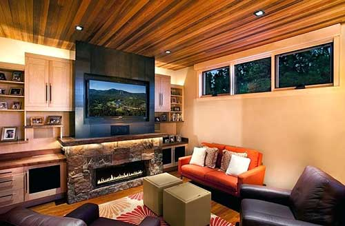 lareira de pedra na sala com tv e teto de madeira