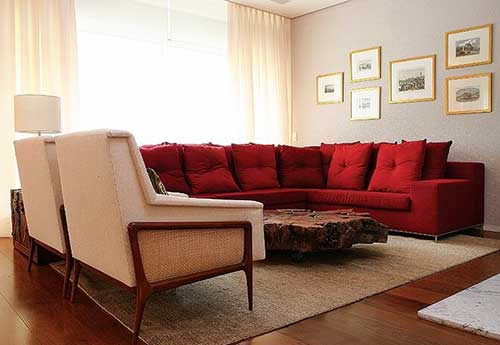 sala de estar com sofa em l vermelho e mesa de centro de madeira marrom