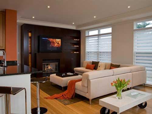 sala de estar de apartamento com tv e lareira conjugada a outros espaços