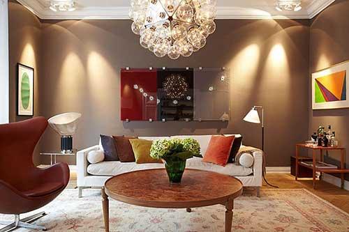 projeto de sala de estar com parede marrom e decoracao colorida