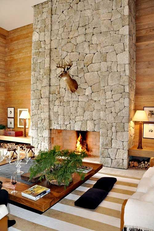 sala de estar com parede de tijolos em pedra e revestimento das paredes em madeira