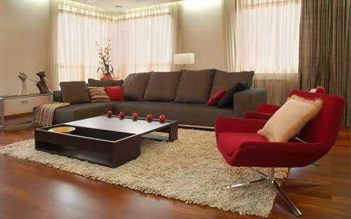 sala de estar decorada com tapete bege, sofa marrom e poltrona vermelha