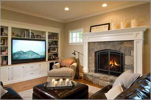 sala de estar com tv, lareira de pedra e poltrona