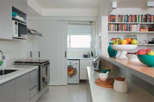 cozinha americana pequena com porta de correr separando ela da area de serviço