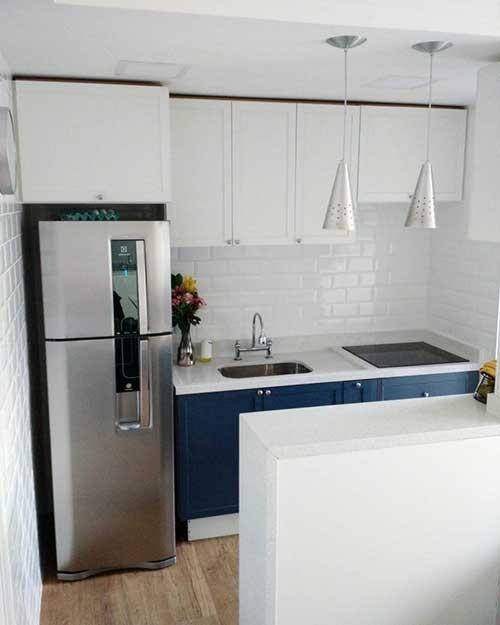 cozinha branca com armario azul e piso amadeirado