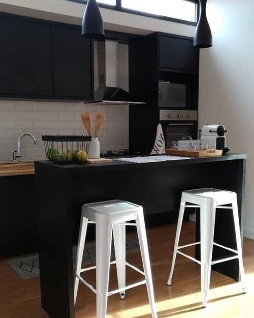 cozinha toda preta com bancos brancos para equilibrar