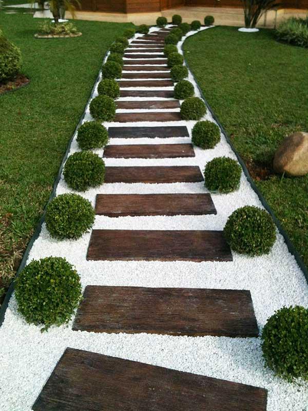 a pedra dolomita combinou bem com as tábuas de madeira e as plantinhas e criou uma elegante passagem no gramado do jardim
