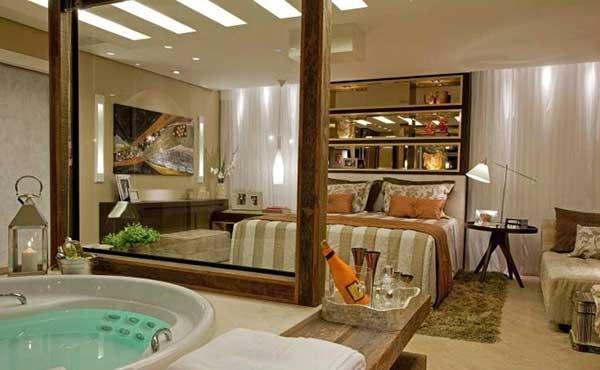 quarto com suíte bege e divisória de vidro para o banheiro com hidromassagem
