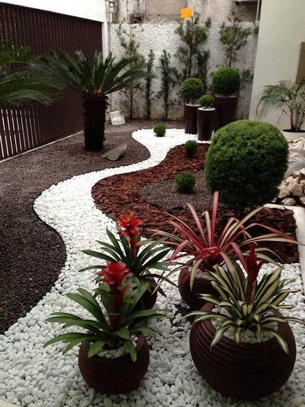 um jardim de inverno bem grande, com pedras brancas e marrons, além de muitos vasos de planta para dar vida ao espaço