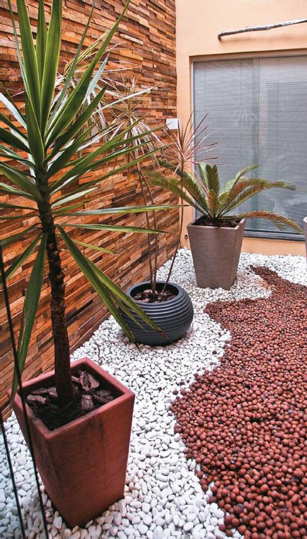 jardim de inverno com seixos e pedras brancas, combinando com a parede amarronzada