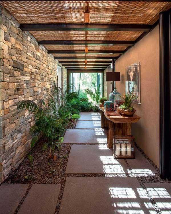 nesse corredor externo com jardim, as pedras serviram de passagem e revestimento para as paredes, combinando bem com a cobertura rústica