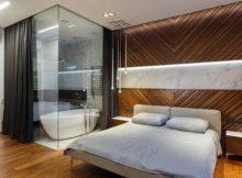 notar que o granito que ornamenta a parede do banheiro continua na parede do quarto, revelando a integração da suíte