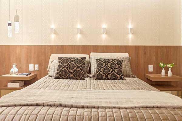 arandelas modernas sobre o painel da cama do quarto do casal
