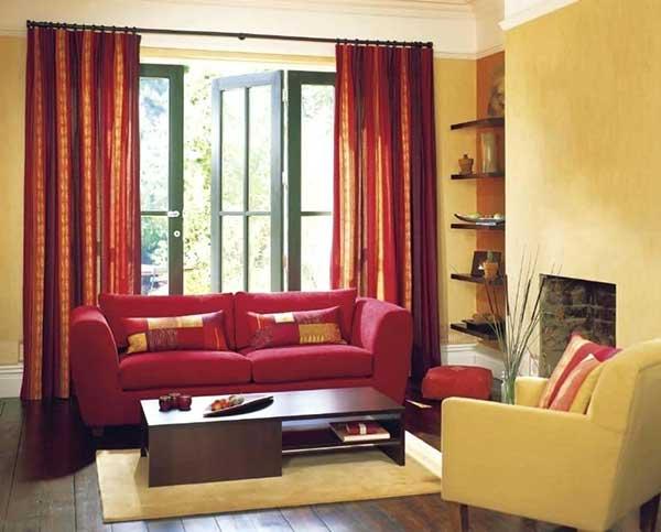 nessa sala vermelha e amarela, a cortina e o sofá combinam bem com o resto da decoração