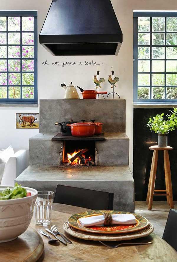 o cimento queimado é um revestimento moderno que pode ornamentar o fogão à lenha e que vai ampliar a aparência campestre da sua cozinha