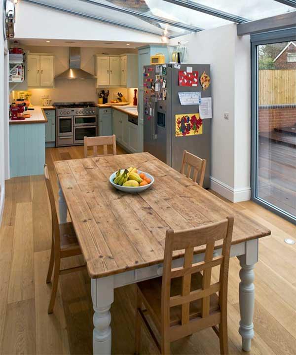 a mesa em madeira de demolição harmonizou bem com essa pequena cozinha externa de sítio