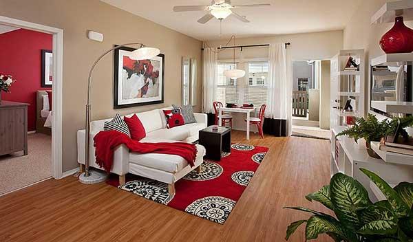 nesta sala de estar, para evitar muita neutralidade graças ao predomínio de tons terrosos, usou-se vermelho na manta, almofadas e tapete