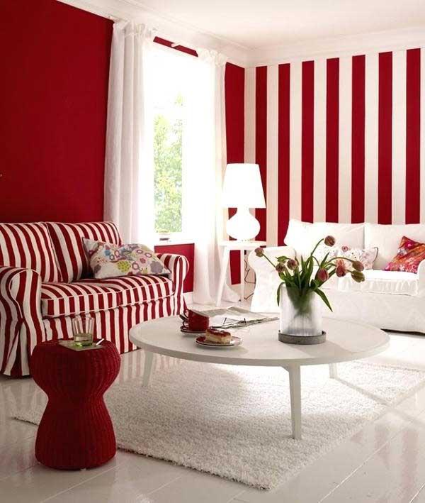 a ideia para criar um contraste interessante aqui foi reproduzir no sofá a textura listrada vermelha e branca do papel de parede