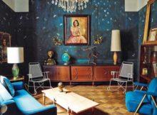 ambiente contando com estilos retro e vintage na decoração, captados a partir do modelo dos móveis, do papel de parede, do candelabro e do grande espelho sobre o móvel